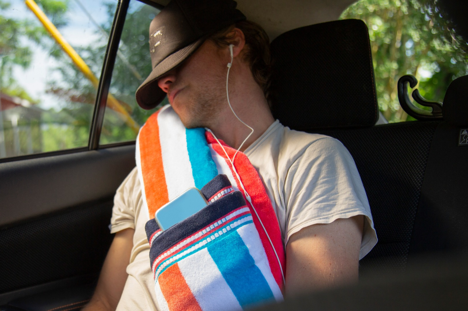 Man wearing a hat pulled over his eyes, sleeping in a car, wearing headphones, resting head against a colorful neck pillow.